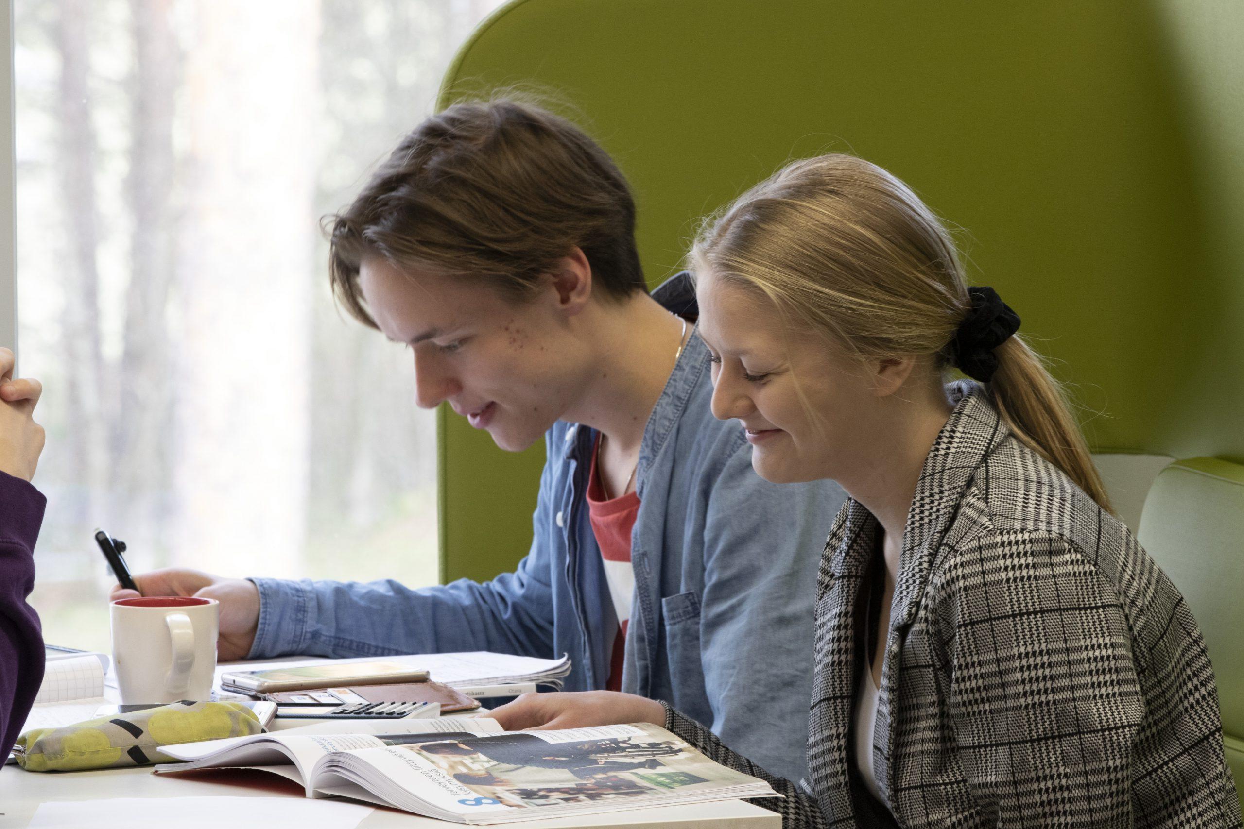 Poika ja tyttö istuvat vierekkäin ja lukevat oppikirjaa, kuva