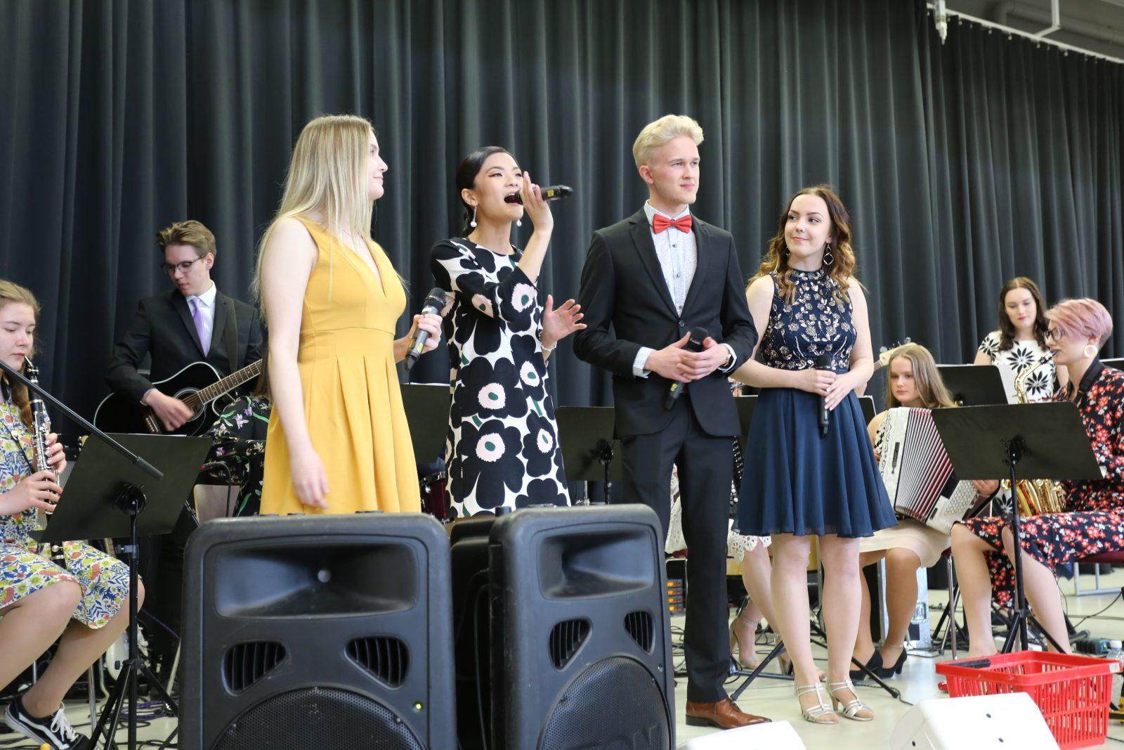 Lukion bändi esiintyy valmistujaisjuhlassa, yksi laulaa mikrofoniin, kuva