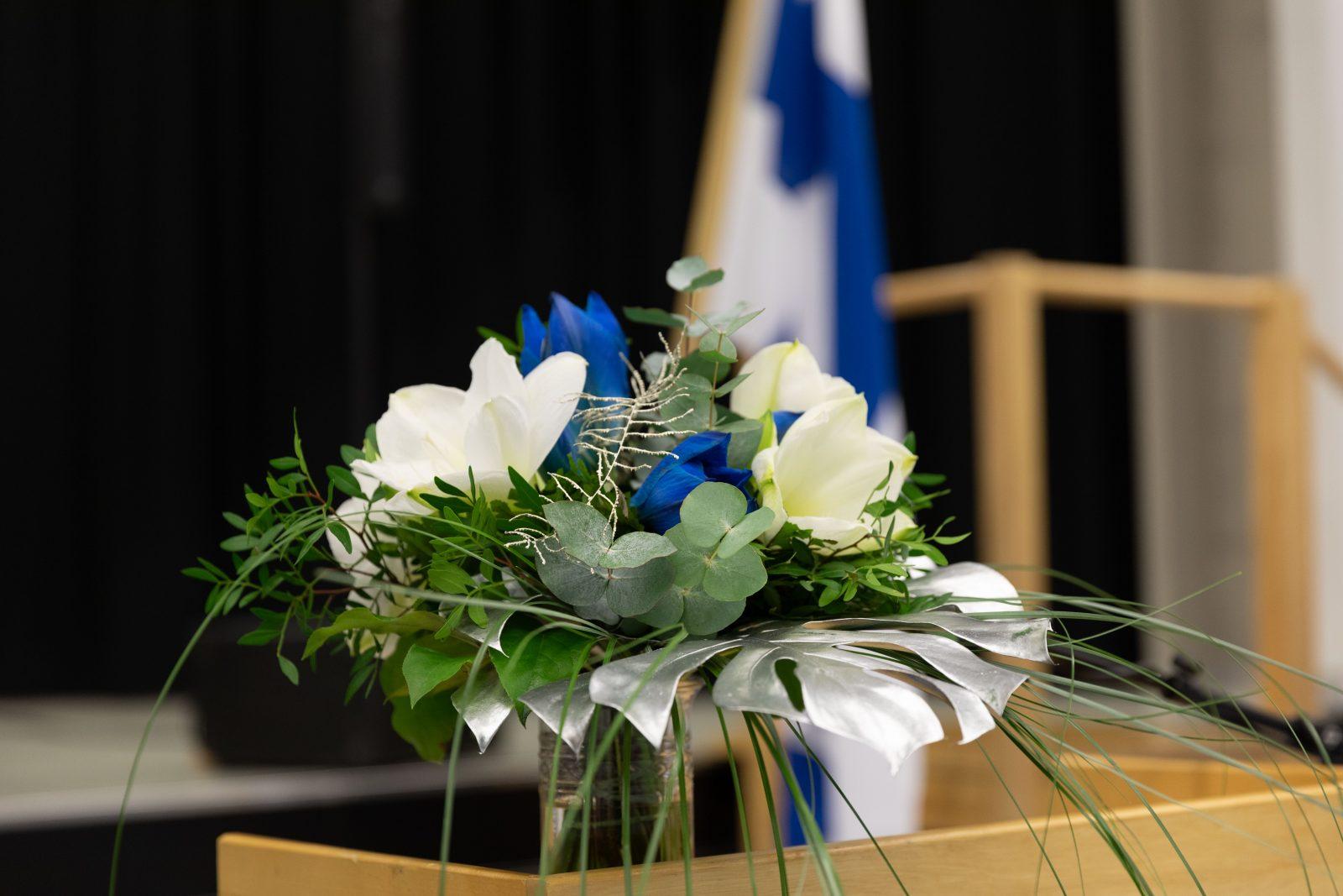 Ylioppilasjuhlien sinivalkoinen kukkakimppu pöydällä, kuva