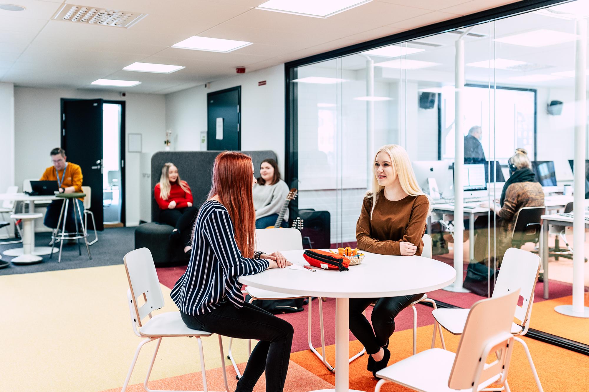 Opiskelijat istuvat uusissa tiloissa pöydän ääressä